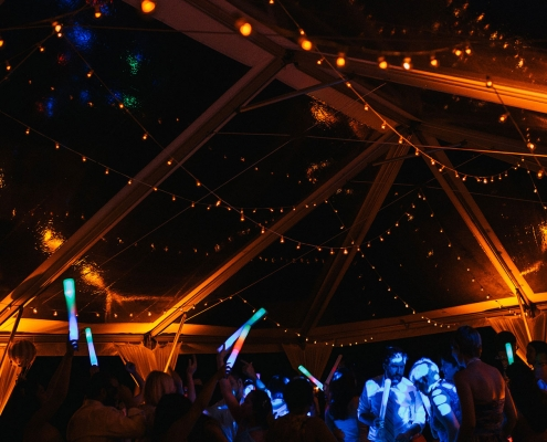 Guests dancing at an outdoor tent wedding reception in Hawaii at Loulu Palm Estate by Destination wedding planner Mango Muse Events creator of Passport to Joy