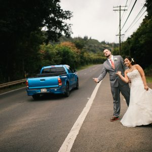 Bride and groom pretend hitch hiking at their Hawaii destination wedding by Destination wedding planner Mango Muse Events creator of Passport to Joy