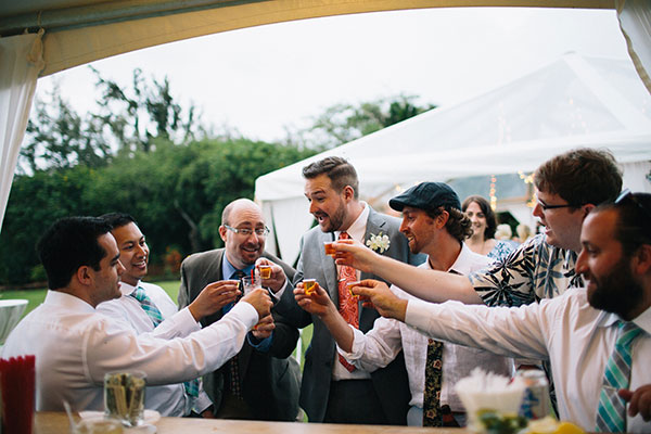 Groom and guests toasting at the wedding bar at a Hawaii destination wedding by Destination wedding planner Mango Muse Events creator of Passport to Joy