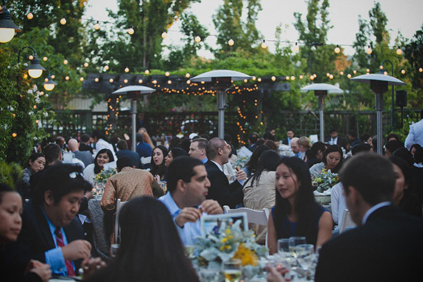 Wedding guests enjoying dinner at an outdoor wedding reception at the Los Altos History Museum by destination wedding planner, Mango Muse Events creator of Passport to Joy