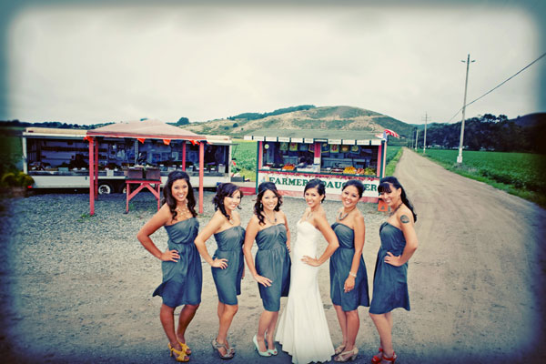 Bride and bridesmaids in grey dresses having fun at a fruit stand at a Half Moon Bay wedding by Destination wedding planner Mango Muse Events creator of Passport to Joy