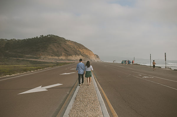 Couple walking at their engagement session by the beach in Southern California