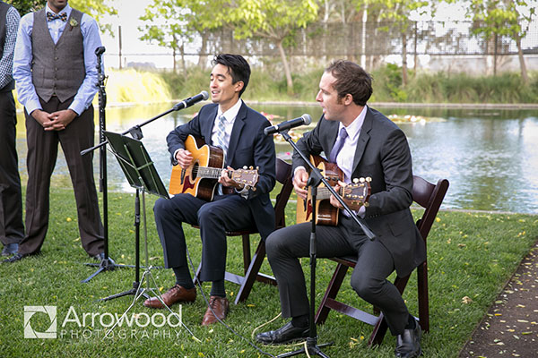 Two friends singing and playing at a personal wedding ceremony in Sonoma at Cornerstone by Destination wedding planner Mango Muse Events creator of Passport to Joy