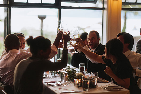 Happy guests clinking glasses at a destination wedding reception in Vancouver by destination wedding planner, Mango Muse Events creator of Passport to Joy