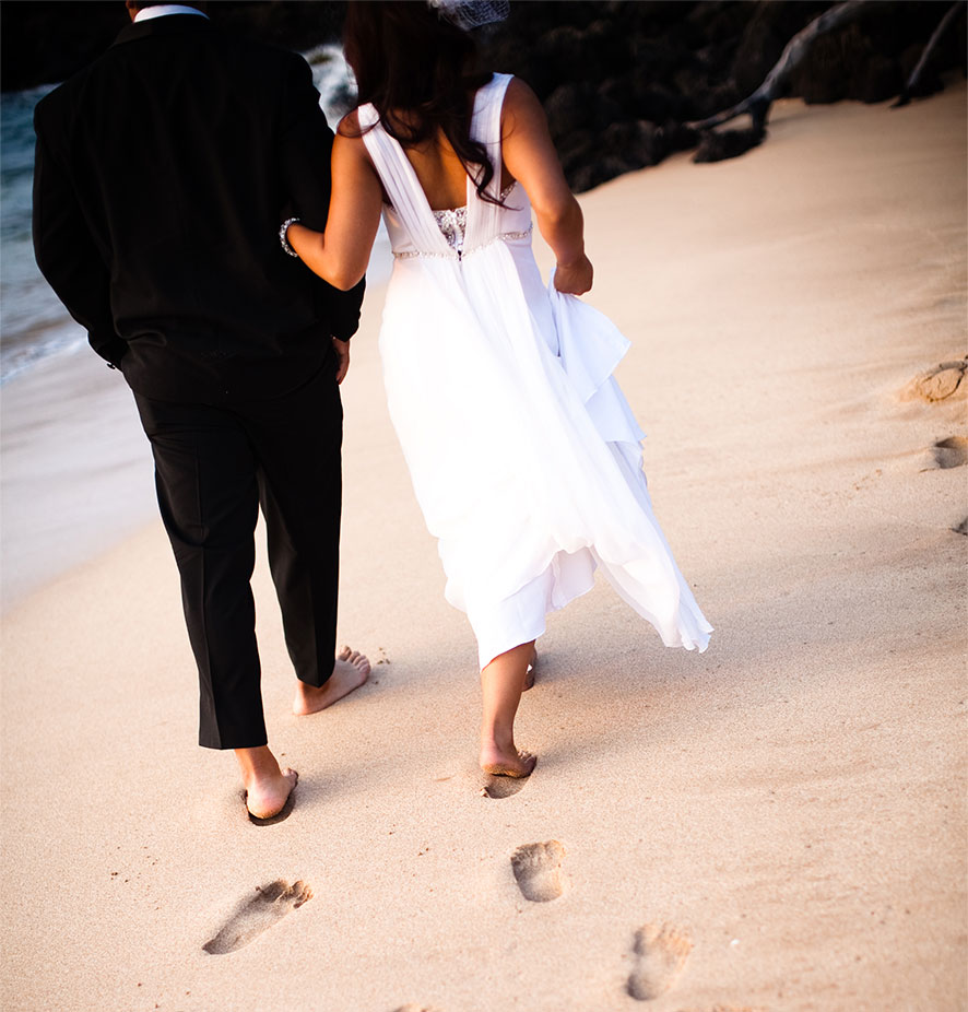 Couples walking on the beach at their Maui beach wedding by destination wedding planner Mango Muse Events creator of Passport to Joy an online wedding planning program
