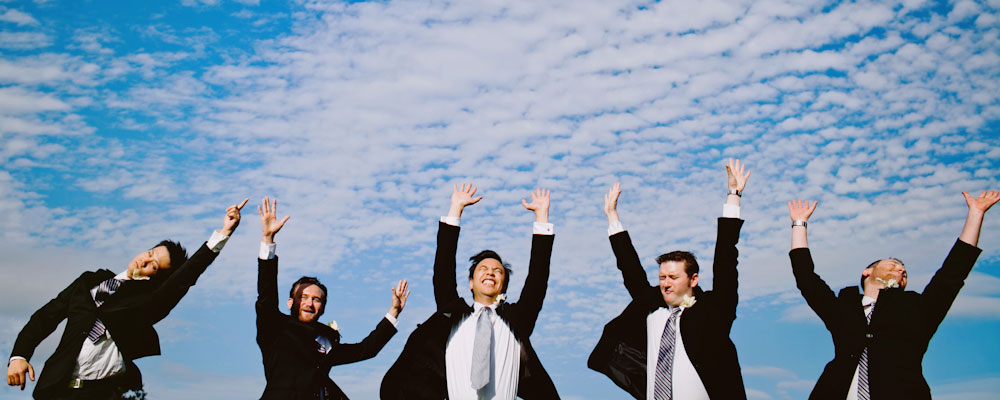 Groom and groomsmen jumping with joy at San Francisco wedding by Destination wedding planner Mango Muse Events creator of Passport to Joy the online wedding planning program