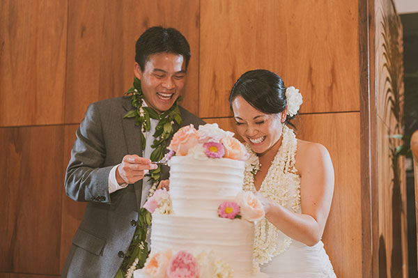 Bride and groom cutting the cake at their wedding in Hawaii by destination wedding planner Mango Muse Events creator of Passport to Joy online wedding planning program