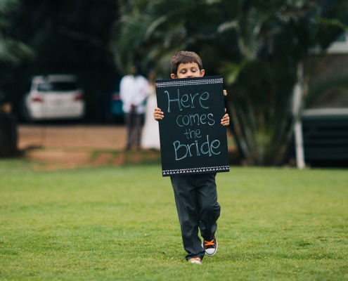 Ring bearer with here comes the bride wedding sign at a Hawaii wedding ceremony by Destination wedding planner Mango Muse Events, creator of Passport to Joy online wedding planning course