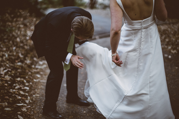 Groom dusting off the bride's wedding dress at an forest wedding by destination wedding planner Mango Muse Events creator of Passport to Joy online wedding planning course