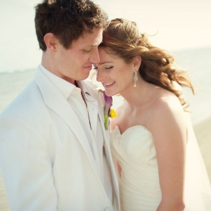 Beach wedding in Hawaii with a happy couple wearing white by destination wedding planner Mango Muse Events creator of Passport to Joy the online wedding planning program for couples