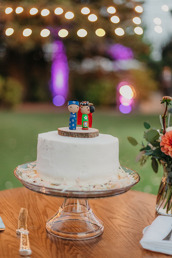 Simple white wedding cake with a cute asian figurine cake topper by destination wedding planner Mango Muse Events creator of Passport to Joy the online wedding planning program