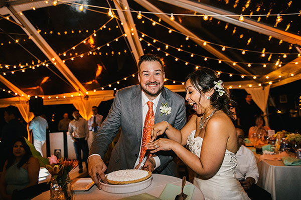 Bride and groom cutting the pie at their wedding reception in Hawaii by destination wedding planner Mango Muse Events creator of Passport to Joy the online wedding planning course for couples