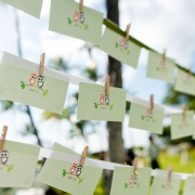 Custom owl designed escort cards on a hanging display at the wedding in Hawaii from Mango Muse Events creator of Passport to Joy the online wedding planning course for couples