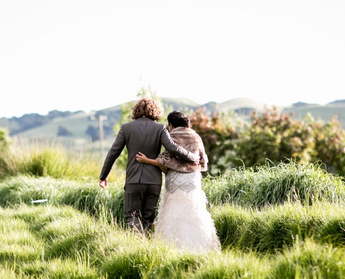 Bride and groom arms around each other walking together in a field at their Sonoma wedding by destination wedding planner Mango Muse Events creator of Passport to Joy, the online wedding planning course for couples