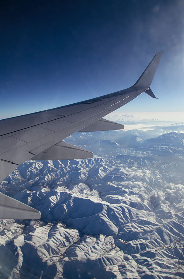 Airplane wing flying over snowy mountains travel