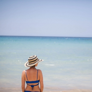 Bride in a blue swimsuit and hat enjoying the beach at her wedding and honeymoon in Hawaii by destination wedding planner Mango Muse Events creator of Passport to Joy, the online wedding planning course for couples
