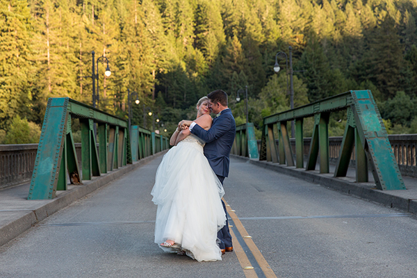 Couple dancing on an empty bridge at sunset on their wedding day in Monte Rio by destination wedding planner Mango Muse Events creator of Passport to Joy the online wedding planning program for couples