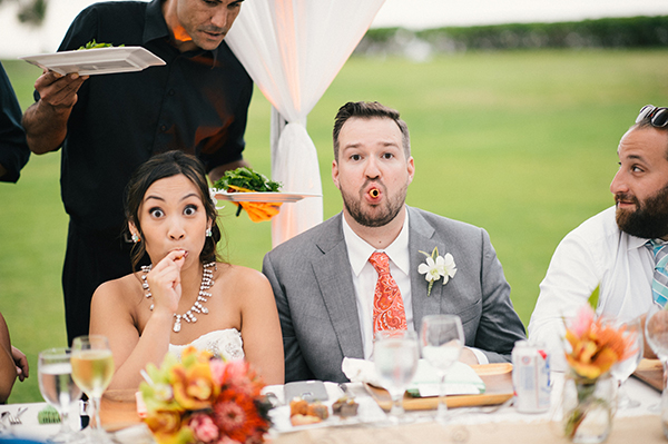 Bride and groom having fun and making a funny face during their wedding reception dinner in Hawaii by destination wedding planner Mango Muse Events creator of Passport to Joy the online wedding planning course for couples