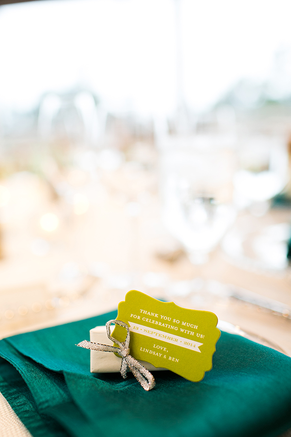 Small wedding favor box with green tag on a teal napkin by wedding planner Mango Muse Events creator of Passport to Joy the online wedding planning course for couples