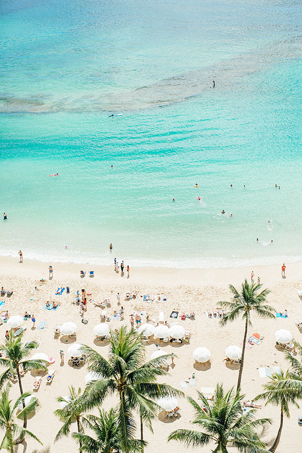 Waikiki beach and tourists sunbathing at a wedding and honeymoon in Hawaii by destination wedding planner Mango Muse Events creator of Passport to Joy, the online wedding planning course for couples