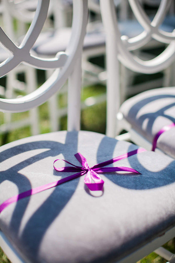 White chair with grey cushion and a purple ribbon to reserve it for vip at a wedding ceremony in wine country by San Francisco Bay Area wedding planner Mango Muse Events creator of Passport to Joy the online wedding planning course for couples