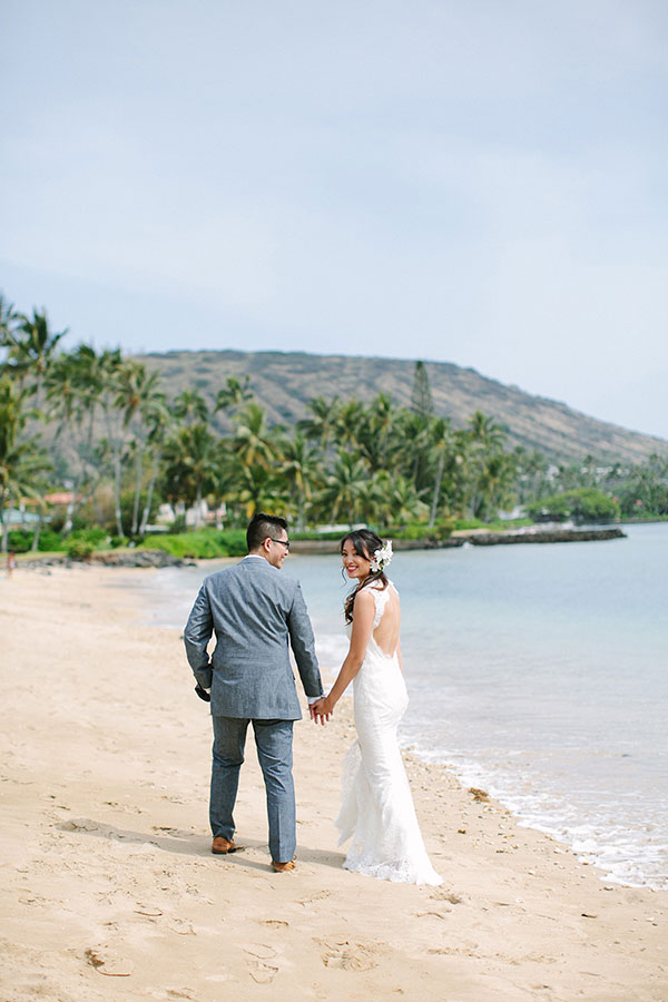 Newlyweds walking on the beach at their tropical beach wedding in Hawaii by destination wedding planner Mango Muse Events creator of Passport to Joy the online wedding planning course for couples