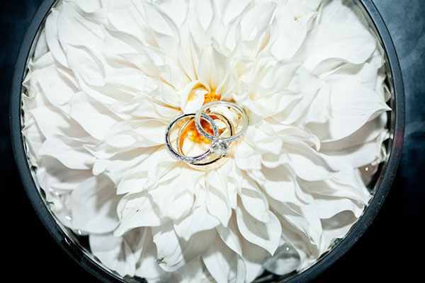 Wedding rings on a white dahlia by destination wedding planner Mango Muse Events creator of Passport to Joy online wedding advisor and planner