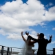 Bride and groom excitedly celebrating on their wedding day by shouting from the rooftop in San Francisco by destination wedding planner Mango Muse Events creator of Passport to Joy online wedding planners and planning course for couples