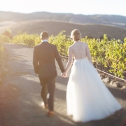 Bride and groom walking in a vineyard at their Sonoma wine country wedding by destination wedding planner Mango Muse Events creator of Passport to Joy online wedding planners and planning course for couples