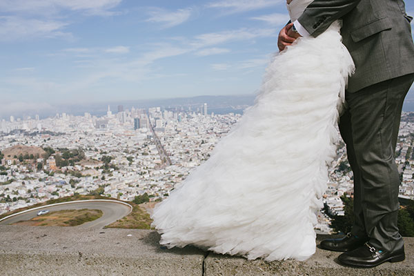 Bride and groom hugging at the city edge in San Francisco at this wedding with a view by destination wedding planner Mango Muse Events creator of Passport to Joy online wedding planning course for couples