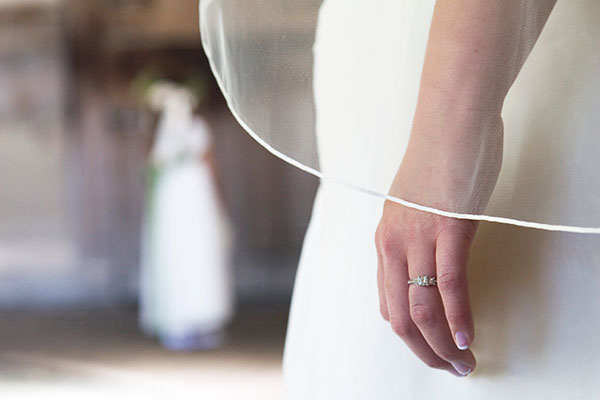 Bride on her wedding day wearing her square diamond engagement ring with planning tips by Passport to Joy online wedding planning course for couples