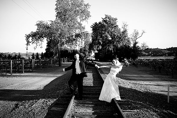 Bride and groom having fun on the train tracks at their wine country wedding by destination wedding planner Mango Muse Events creator of Passport to Joy online wedding planning course for couples