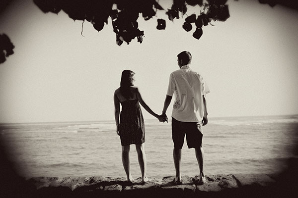 Engagement photos taken on the beach in Hawaii looking out at the ocean planning tips by online wedding planners, Passport to Joy
