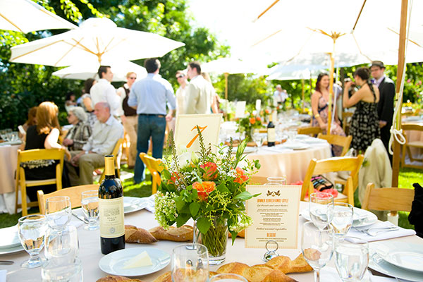 Wedding reception table with an orange floral centerpiece for a summer garden wedding by destination wedding planner Mango Muse Events creator of Passport to Joy the online wedding planning course for couples