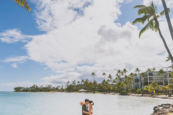 Bride and groom enjoying at moment at their beach wedding at the Kahala hotel on Oahu by destination wedding planner Mango Muse Events creator of Passport to Joy the online wedding planning course for couples