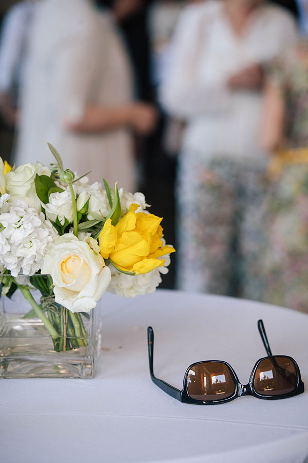 Sunglasses and white and yellow floral centerpiece for a day time wedding in Hawaii by destination wedding planner Mango Muse Events, creator of Passport to Joy online wedding planners