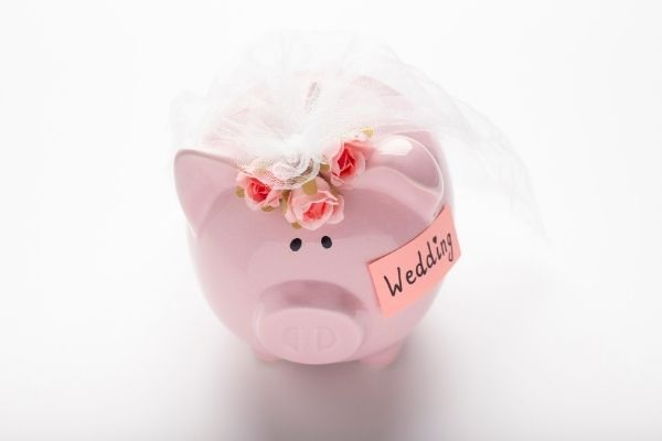 Pink piggy bank with bridal veil tips for help your wedding budget by Passport to Joy online wedding planners