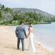 Newlyweds walking on the beach at their private estate beach wedding in Hawaii by destination wedding planner Mango Muse Events creator of Passport to Joy the online wedding planners