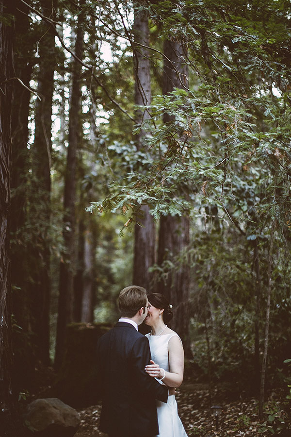 A bride and groom kiss amoungst the redwoods at their Ben Lomond forest wedding by destination wedding planner Mango Muse Events creator of Passport to Joy online wedding planners