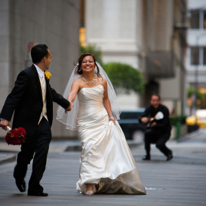 Couple laughing and running with a wedding photographer in the background at a San Francisco wedding by destination wedding planner Mango Muse Events creator of Passport to Joy online wedding planner