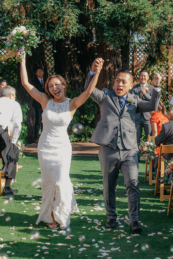 Excited bride and groom newlyweds just married and celebrating down the aisle at their wedding ceremony by destination wedding planner Mango Muse Events creator of Passport to Joy, online wedding planners